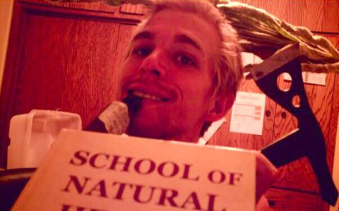 Jason Kvestad holds a School of Natural Health book