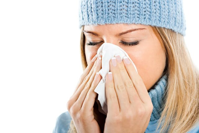 A young woman blows her nose from the flu