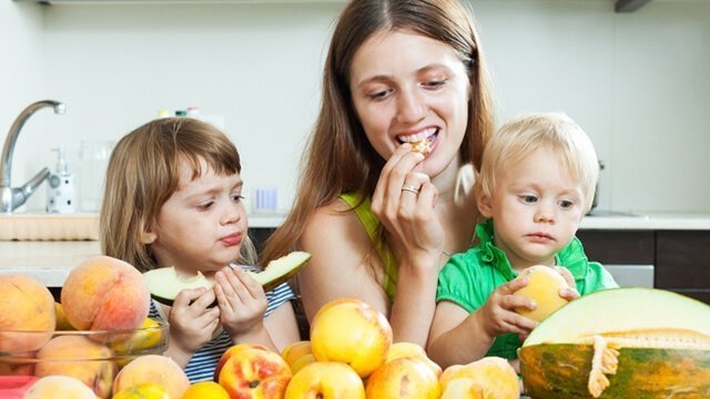 Family eating fruit in a kitchen