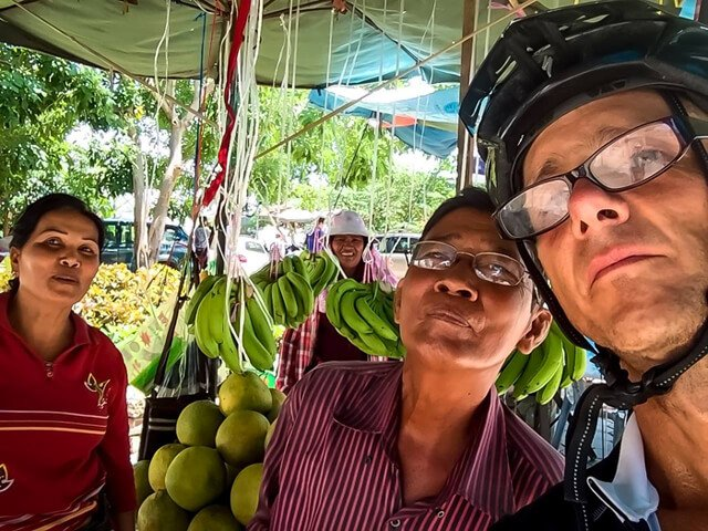 Mark Tassi photographs himself and two others at a fruit market in Cambodia