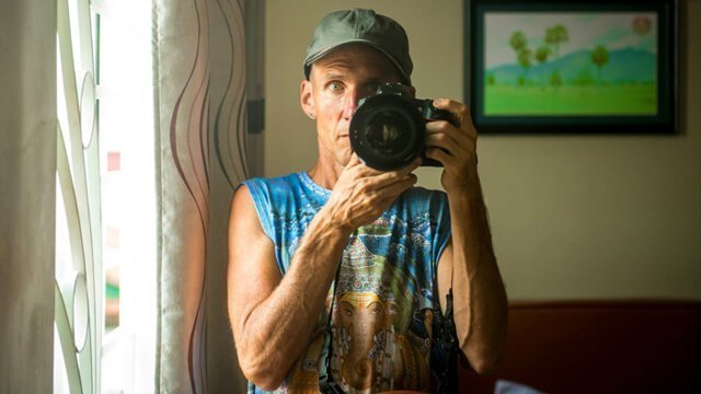 Mark Tassi photographs himself in a mirror in Cambodia