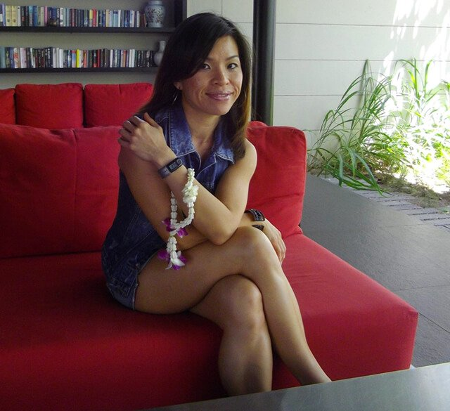 Mewsum Wong is photographed while seated on a red couch