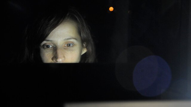 A woman reads from a computer screen in a dark room