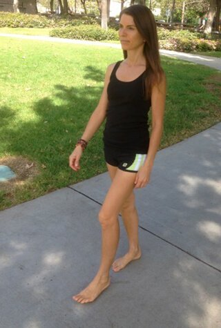 Alicia Grant walks barefoot along a sidewalk