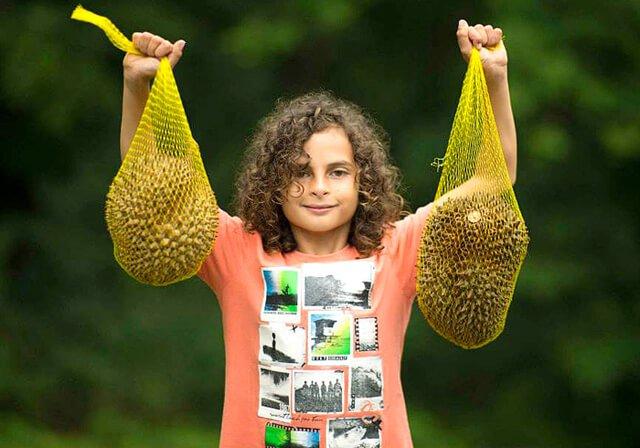 Cappi Osborne raises high two durians at The Woodstock Fruit Festival in 2014