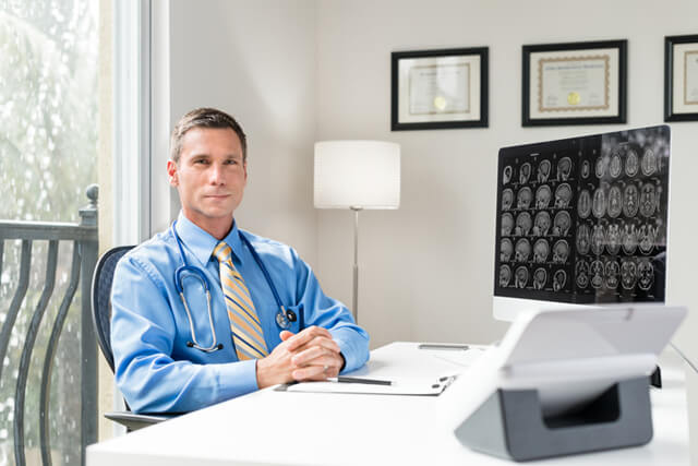 A doctor sits behind a desk in an office