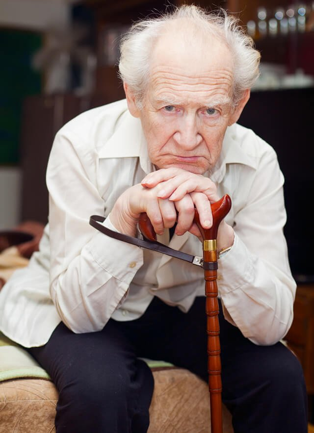 Unhappy old man leers while hunched over a cane