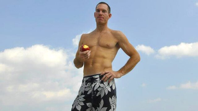 Korey Constable eats an apple with the sky as a background