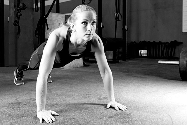 Young woman performing push-ups in a gymnasium