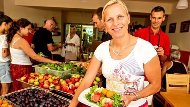 A woman fills her plate with food at the Fruits and Health Festival