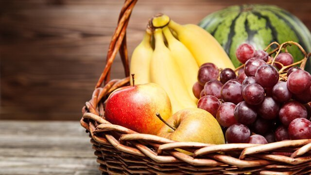 A basketful of bananas, grapes, apples and watermelon