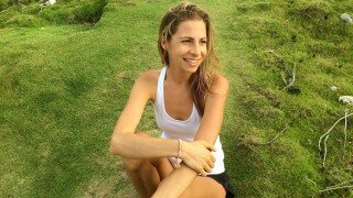 Kat Green sitting on a hilly field