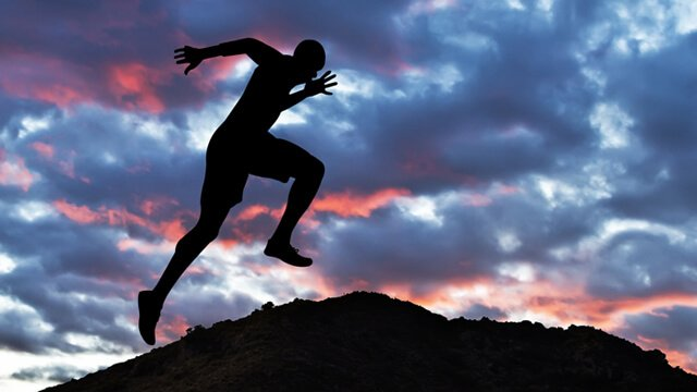 Man reaching the top of a hill