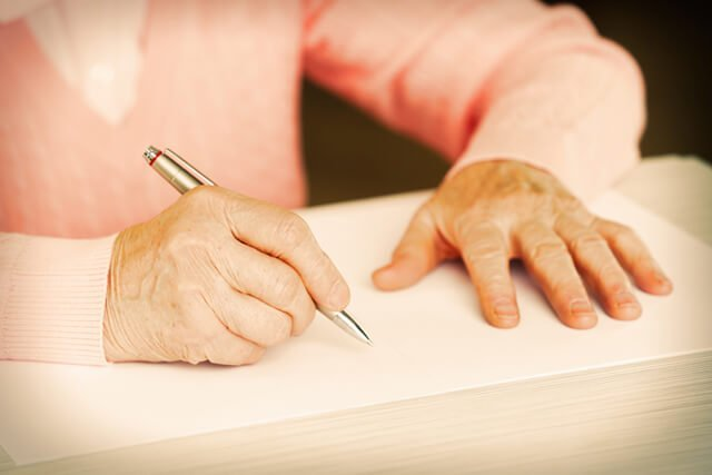Closeup of the hands of an adult woman writing with a pen on a table