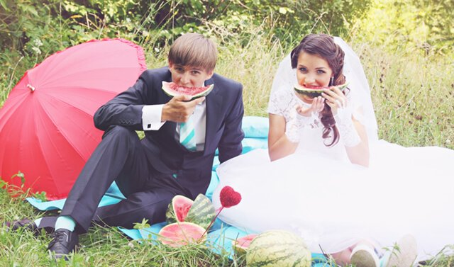 A bride and groom eat large watermelon slices while sitting on a blanket on grass