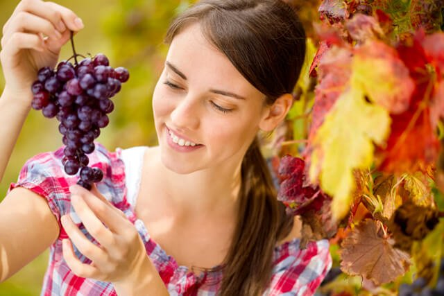 Cheerful young woman looking at bunch of red grapes