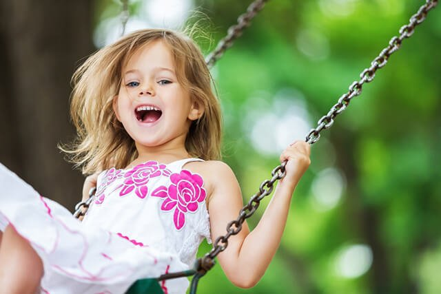 Young girl having fun on a swing set