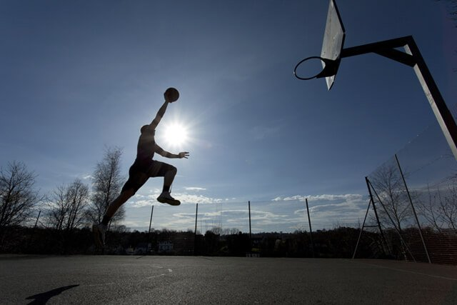 Silhouette of a basketball player taking off to slam dunk