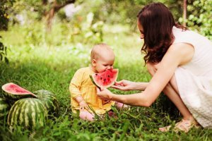 Mother feeds a toddler watermelon on grass