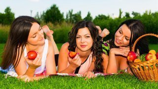 Young women enjoy fruit while laying on grass