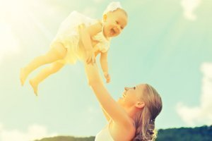 Woman raises high her baby daughter