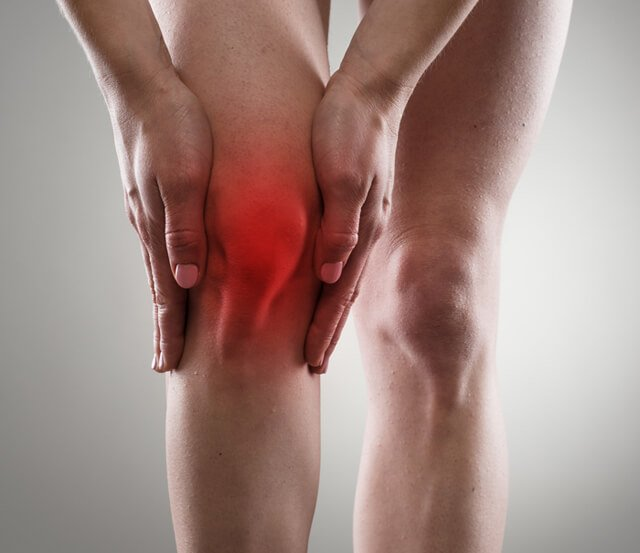 Woman touches her inflamed right knee