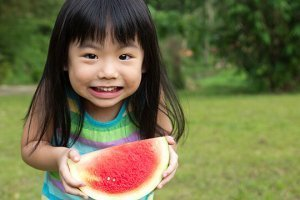A young Asian girl eats watermelon outside