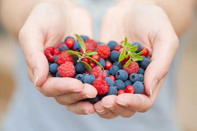 A woman holds fresh berries