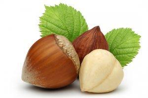 Whole and shelled hazelnuts on white background