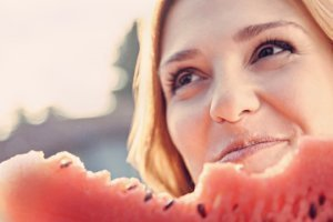 A closeup of a woman enjoying watermelon
