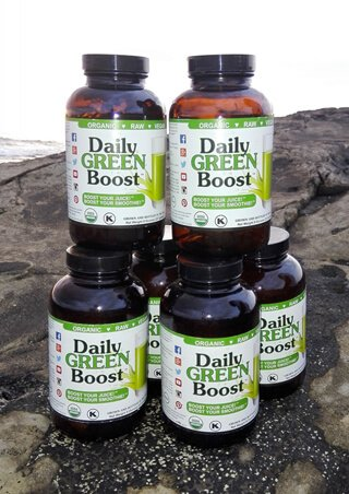 Bottles of Daily Green Boost on a rock at a beach