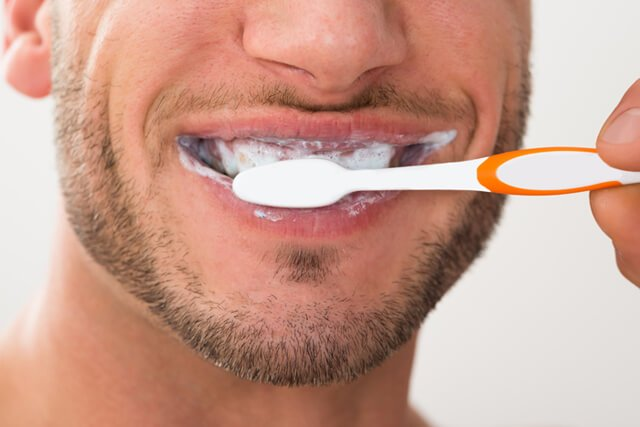Closeup of a man brushing his teeth