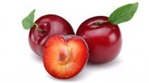 Red plums whole and halved on white background