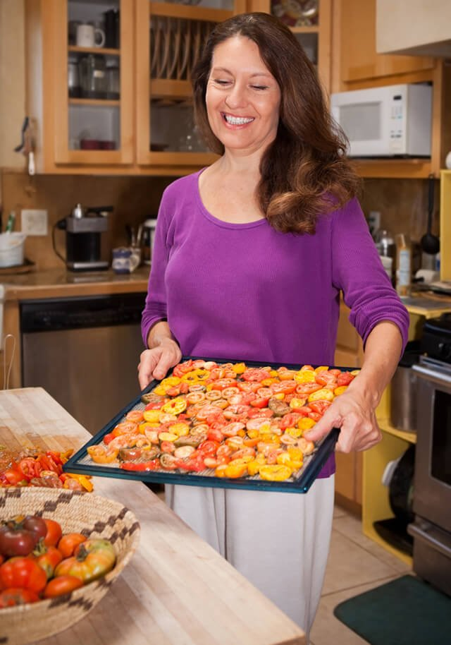 Woman holds a dehydrator rack full of heirloom tomatoes