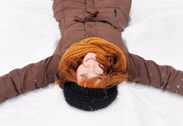 Young woman makes snow angels