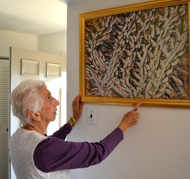 Betty Korba points to a painting of hers