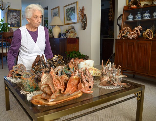 Betty Korba shows sea creature sculptures on a table