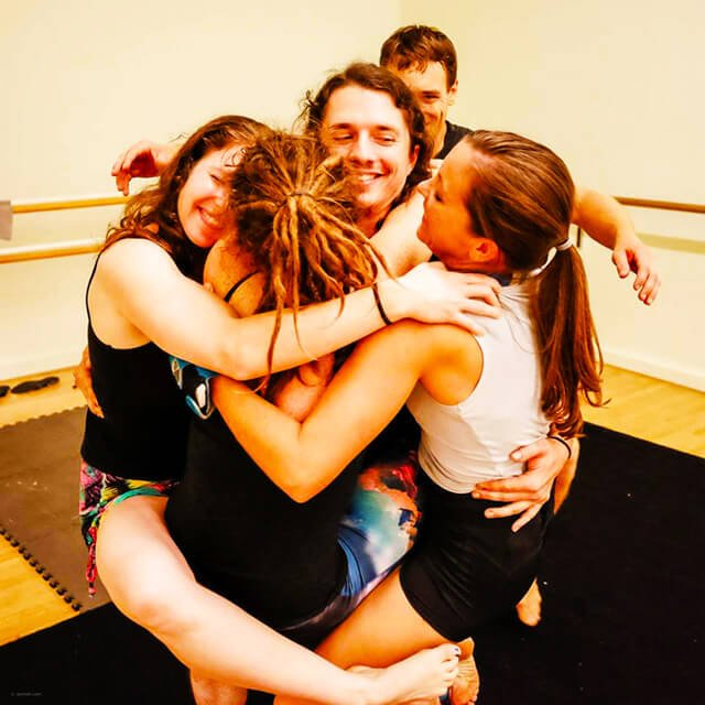 Brittany Taylor is wrapped in a group hug with acro practitioners