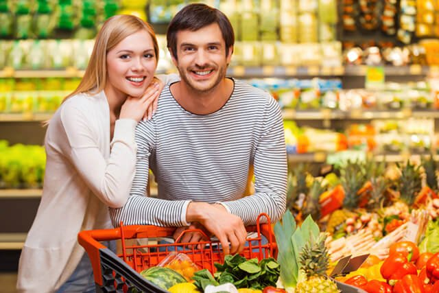 A man and woman shop for fruits and vegetables