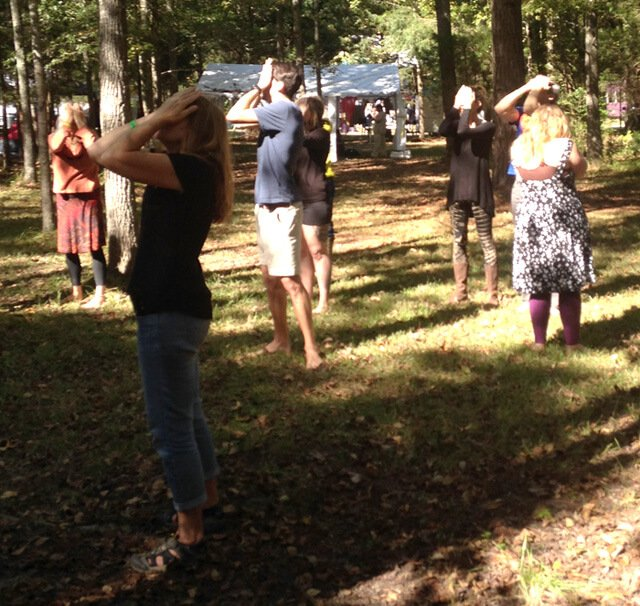 Nathan Oxenfeld leads a palming practice at the Shakori Hills Grassroots Festival in Silk Hope, North Carolina