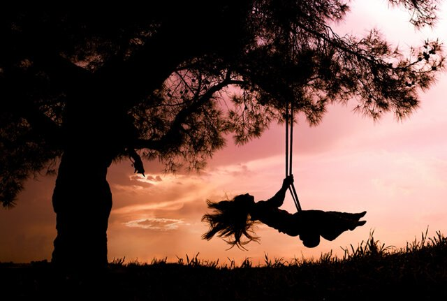 Silhouette of a young woman on a swing with sunset background