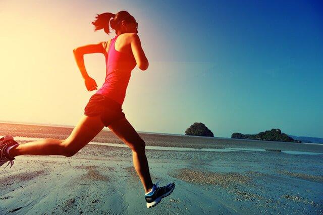 Woman runs along a beach at sunrise