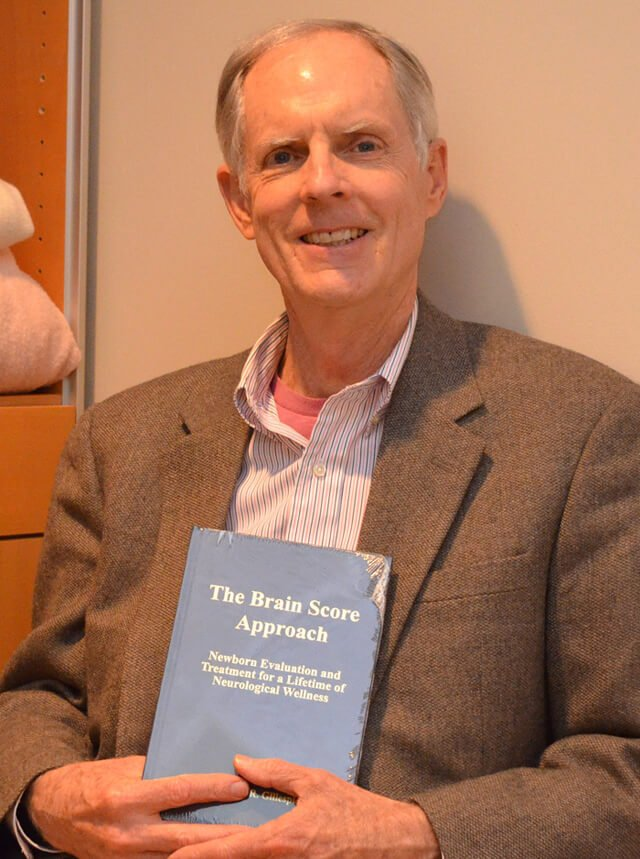 Dr. Barry Gillespie holds a copy of his book The Brain Score Approach