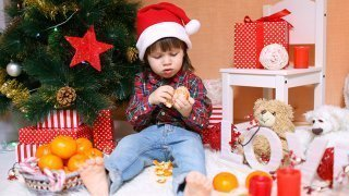 A boy peels an orange next to a Christmas tree