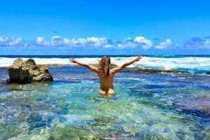 Katy Craine naked with arms raised in the Pacific Ocean