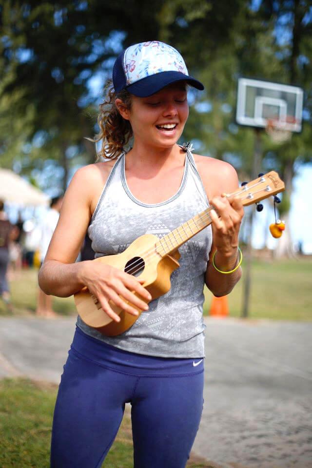 Katy Craine plays a ukulele while standing