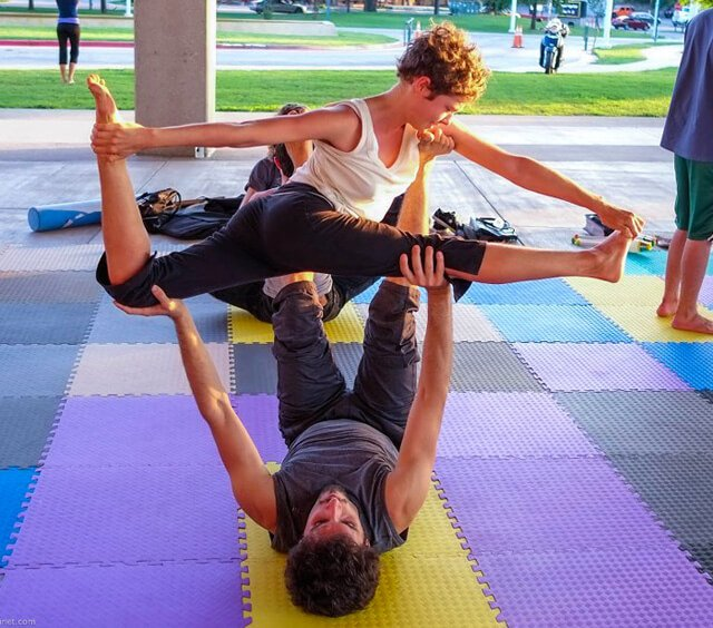 Katy Craine practices acro on mats outside