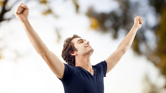 """Man with arms raised in a """"V"""" in nature"""