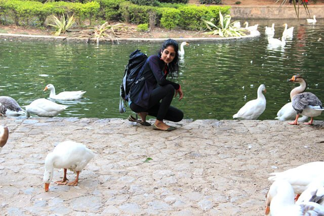 Rupinder Kaur crouches beside a pond