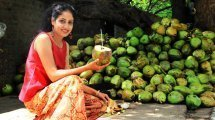 Rupinder Kaur crouches while holding an opened coconut